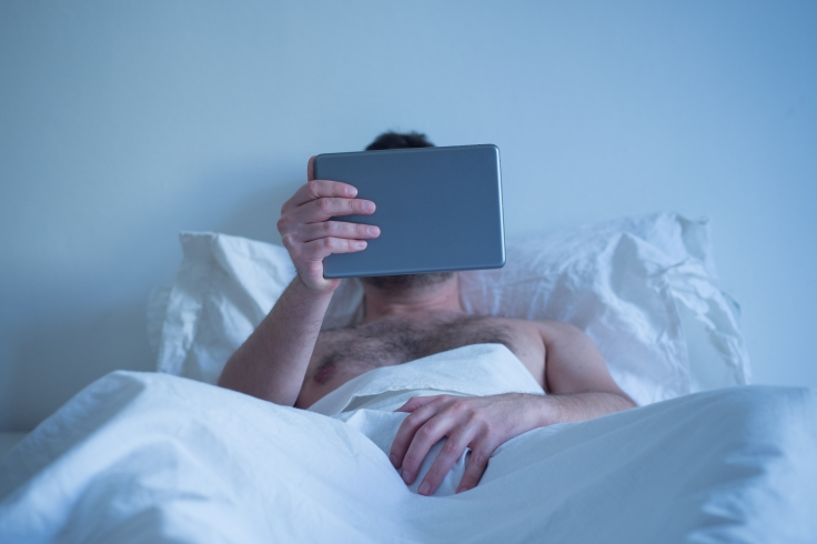 Man lying in the bed , watching porn on the tablet and masturbat